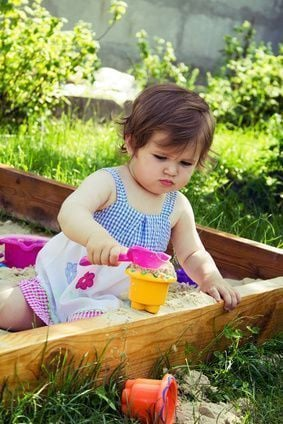 Little cute girl playing in sandbox